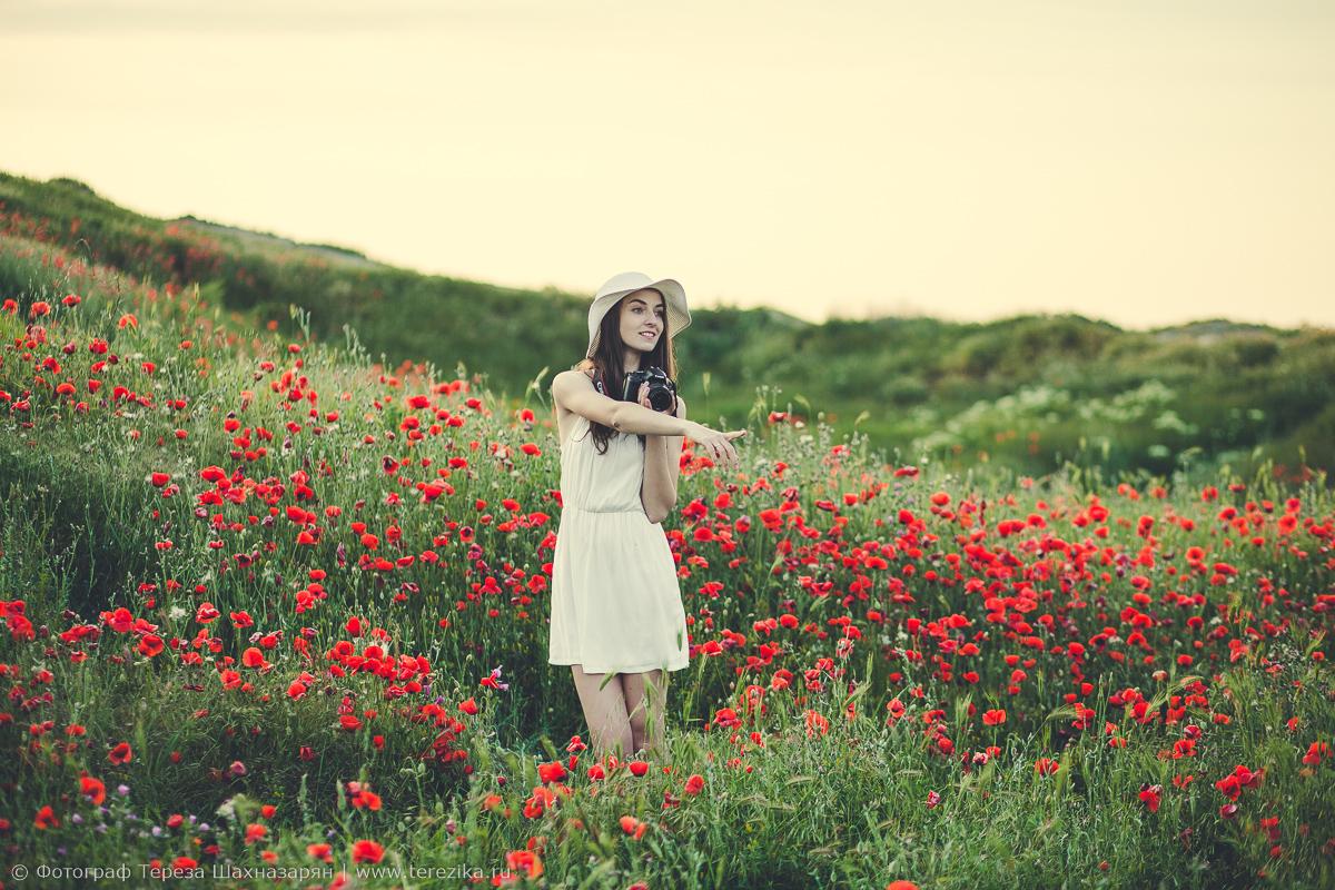 Девушка с камерой на поляне с маками